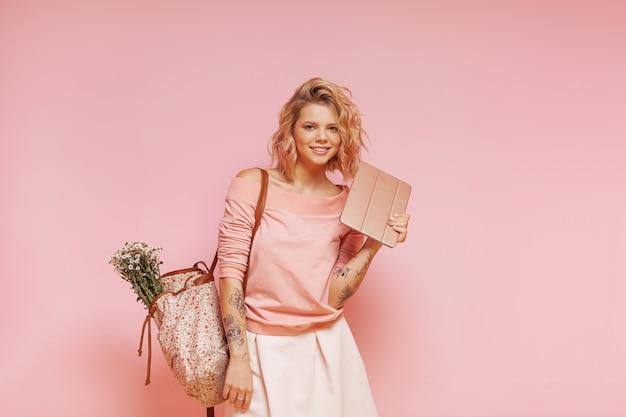 Jovem sorridente mulher estudante hipster com penteado rosa encaracolado colorido e tatuagem segurando o tablet Foto Premium