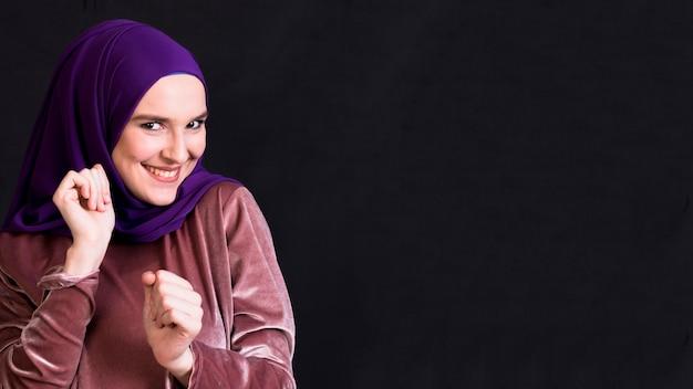 Jovem sorridente mulher muçulmana dançando na superfície preta Foto gratuita