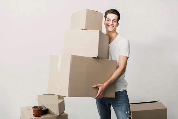 Jovem sorridente segurando caixas de papelão Foto gratuita