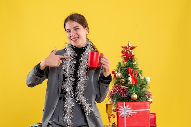 Jovem sorridente segurando um copo vermelho e apontando com o dedo para ela perto da árvore de natal e coquetel de presentes Foto gratuita