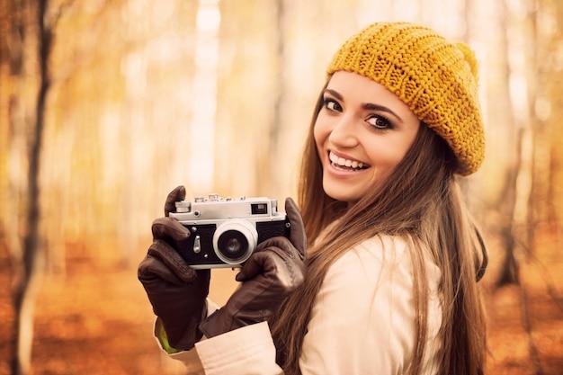 Jovem sorridente segurando uma câmera retro Foto gratuita