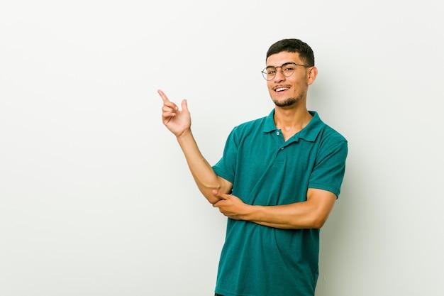 Jovem, sorrindo alegremente apontando com o dedo indicador fora Foto Premium