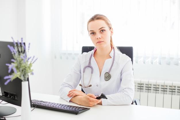Jovem, sorrindo, doutor, sentando, escrivaninha, ligado, um, pretas, cadeira, com, dela, braços cruzaram Foto Premium