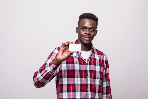 Jovem sorrindo e mostrando o cartão com espaço vazio da cópia. isolado Foto gratuita