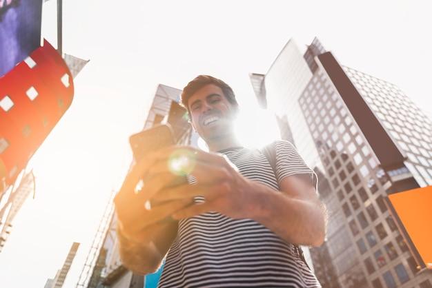 Jovem sorrindo enquanto estiver usando seu smartphone Foto gratuita