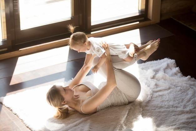 Jovem, sorrindo, yogi, mãe, e, filha bebê, exercitar, casa Foto gratuita