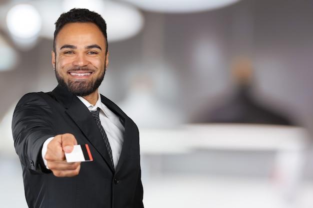 Jovem, sucedido, homem negócios, em, um, elegante, clássicas, pretas, paleto, segurando, um, plástico, cartão crédito Foto Premium