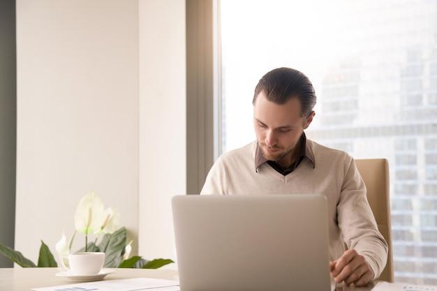 Jovem, sucedido, homem negócios, trabalhando, em, escrivaninha escritório, usando, laptop, computador Foto gratuita