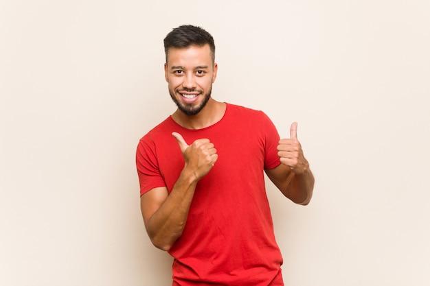 Jovem sul-asiático, levantando os dois polegares, sorrindo e confiante. Foto Premium