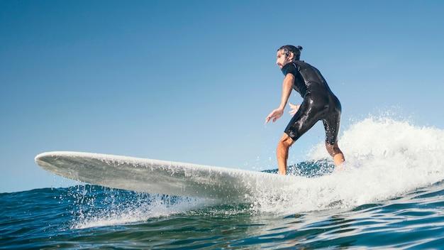 Jovem surfando nas ondas do mar Foto gratuita