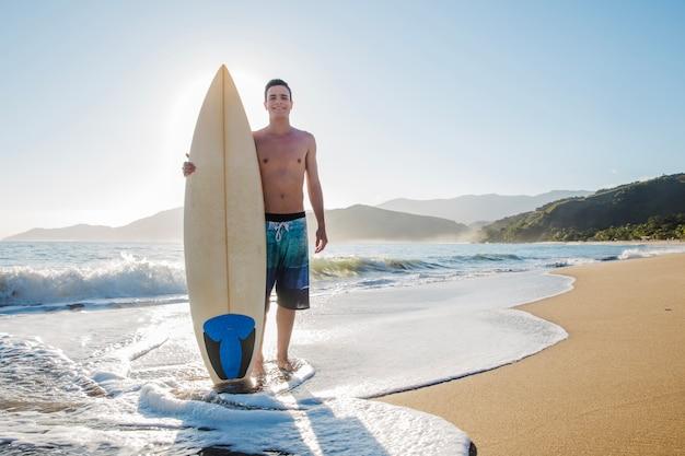Jovem surfista na praia Foto gratuita