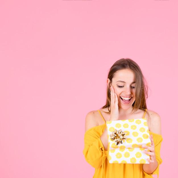Jovem surpreendida abrindo a caixa de presente de bolinhas amarelas com laço dourado Foto gratuita