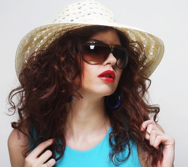 Jovem surpreendida usando chapéu e óculos de sol Foto Premium