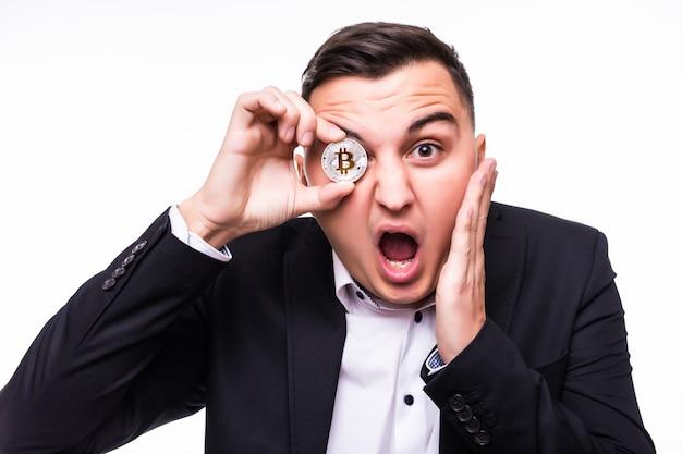 Jovem surpreso em branco com uma moeda de bitcoin nas mãos Foto gratuita