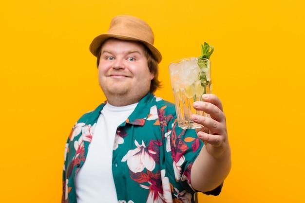 Jovem tamanho grande homem com uma bebida mojito contra parede plana Foto Premium