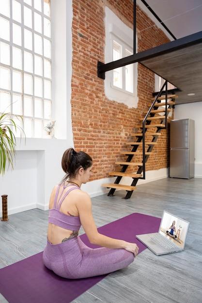 Jovem, tendo uma aula de ioga online em seu laptop. ela está aprendendo em casa. espaço para texto. Foto Premium