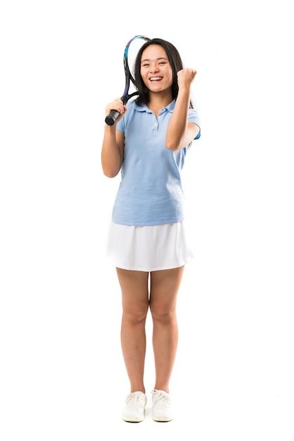 Jovem tenista asiática isolado parede branca comemorando uma vitória Foto Premium