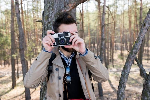 Jovem tirando foto com a câmera na floresta Foto gratuita