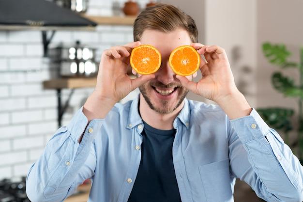 Jovem tirando sarro com duas laranjas fatia em casa Foto gratuita