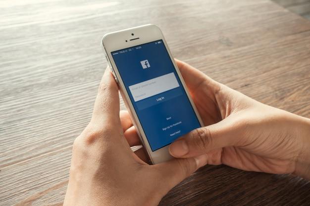Jovem toca ícones do facebook no smartphone Foto gratuita