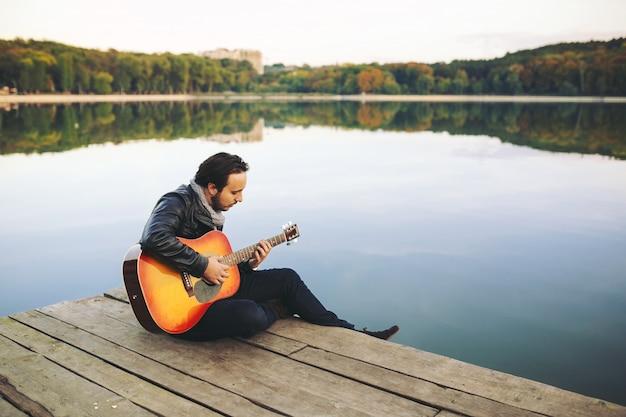 Jovem tocando guitarra no lago Foto gratuita