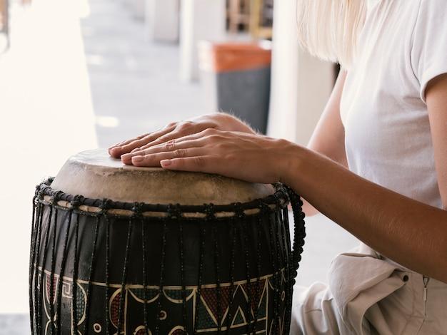 Jovem tocando instrumento de percussão latina Foto gratuita