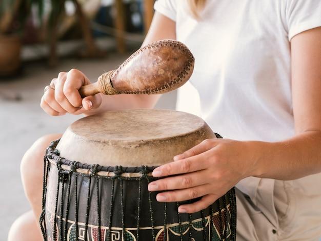 Jovem tocando instrumentos de percussão africanos Foto gratuita