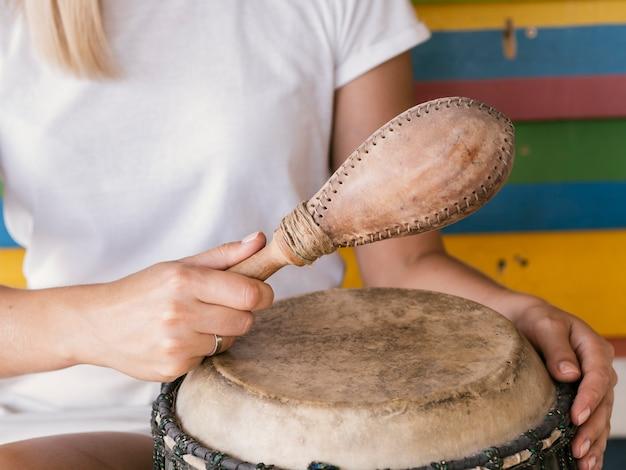Jovem tocando instrumentos de percussão perto de parede multicolorida Foto gratuita