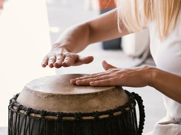 Jovem tocando tambor latino Foto gratuita