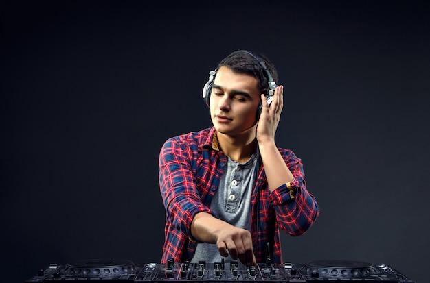 Jovem tocar música no mixer de um dj no estúdio Foto Premium