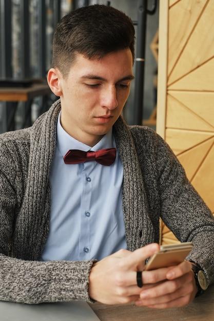 Jovem tomando café no café e usando um telefone celular Foto Premium