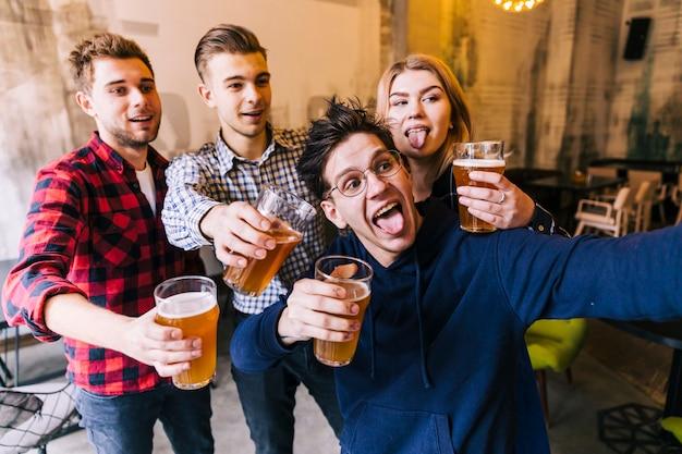 Jovem tomando selfie no celular com seus amigos segurando os copos de cerveja Foto gratuita