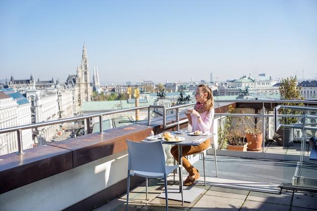 Jovem tomando um café da manhã servido em um telhado do edifício da cidade europeia Foto Premium