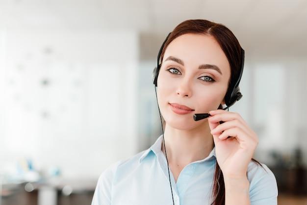 Jovem trabalhador de escritório com um fone de ouvido respondendo em uma chamada cente falando com os clientes Foto Premium