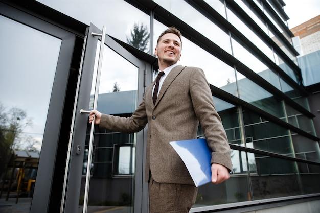 Jovem trabalhador de escritório entrando no prédio com uma pasta na mão Foto Premium
