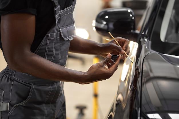 Jovem trabalhador de serviços automotivos afro está pintando detalhes de carros Foto Premium