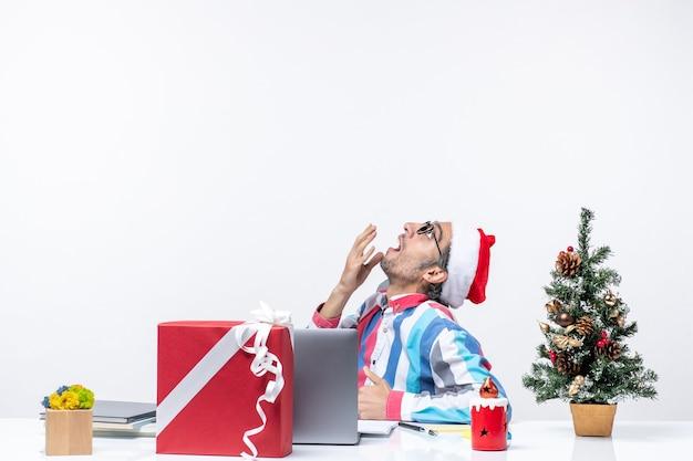 Jovem trabalhador do sexo masculino de vista frontal sentado em seu local de trabalho no fundo branco Foto gratuita