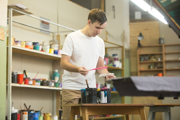 Jovem trabalhador do sexo masculino escolhendo as tintas apropriadas Foto gratuita