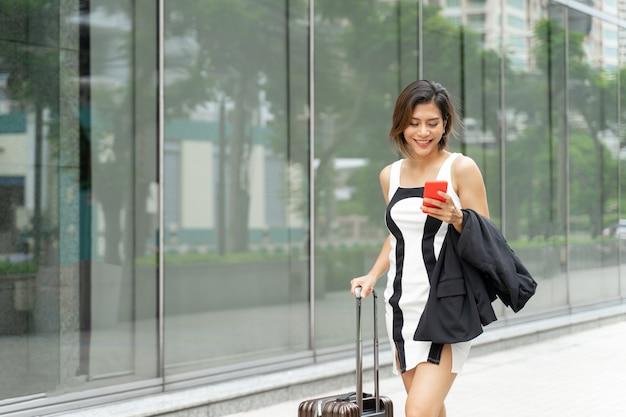 Jovem trabalhadora usa smartphone e caminha com mala Foto gratuita