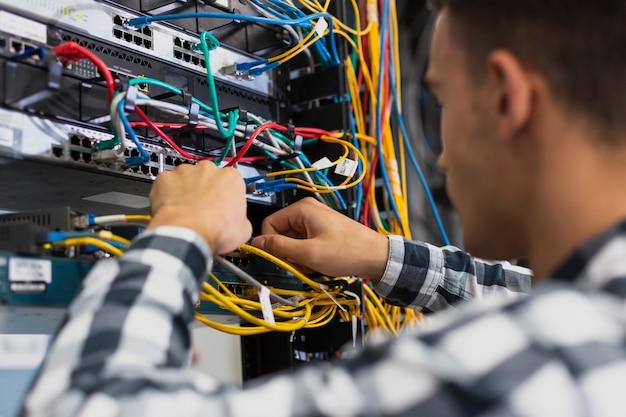 Jovem trabalhando em um interruptor ethernet closeup Foto gratuita