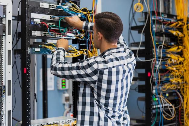 Jovem trabalhando em um interruptor ethernet tiro médio Foto gratuita