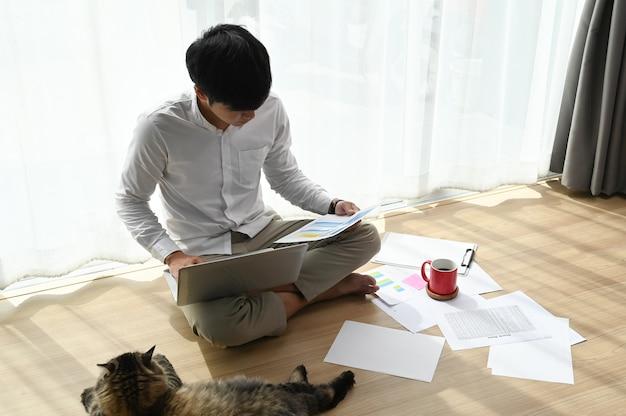 Jovem trabalhando em um laptop e sentado no chão da sala de estar. Foto Premium