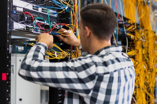 Jovem trabalhando em um switch ethernet Foto gratuita