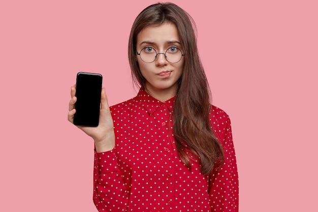 Jovem triste franze os lábios, segura um celular moderno com tela de maquete, usa óculos transparentes e veste uma camisa de bolinhas Foto gratuita