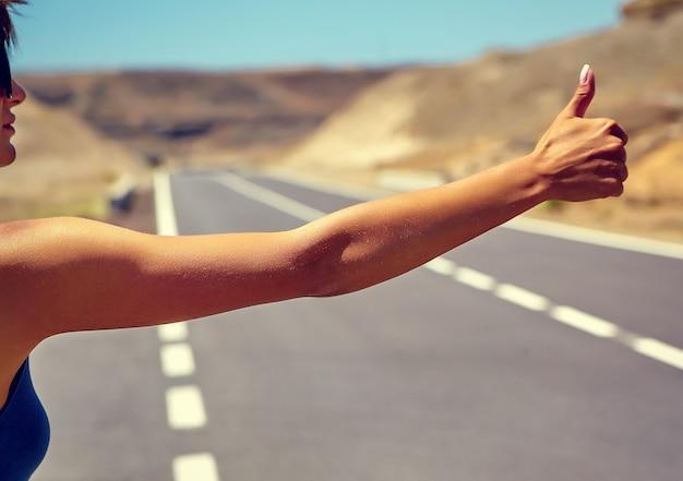 Jovem turista caucasiana pedindo carona ao longo de uma estrada no pôr do sol Foto gratuita