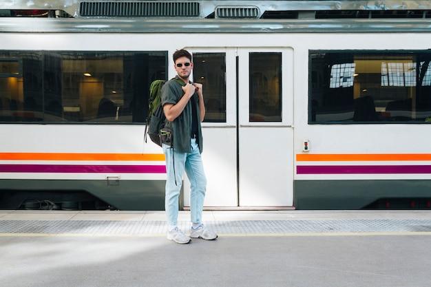 Jovem turista masculina com mochila posando na estação ferroviária Foto gratuita