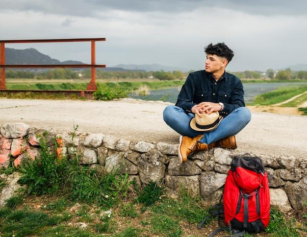 Jovem turista masculina sentado com mochila perto do rio bonito Foto gratuita