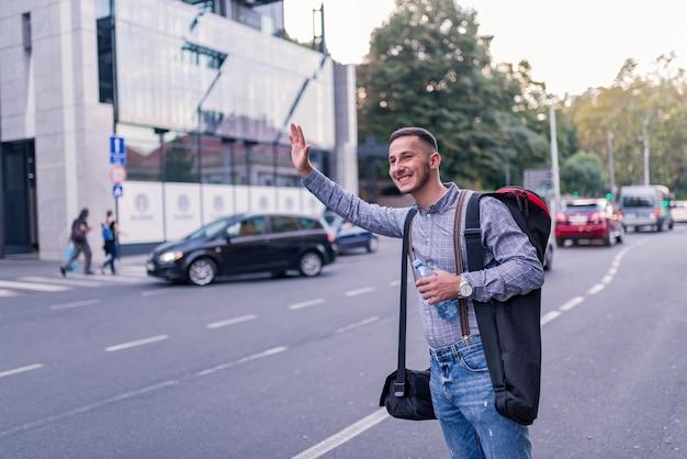 Jovem turista parando um táxi Foto Premium