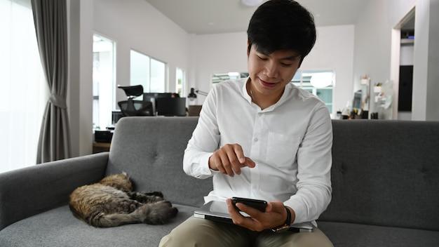 Jovem usando telefone inteligente enquanto está sentado com seu gato no sofá em casa. Foto Premium