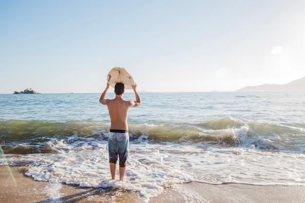Jovem vai surfar Foto gratuita